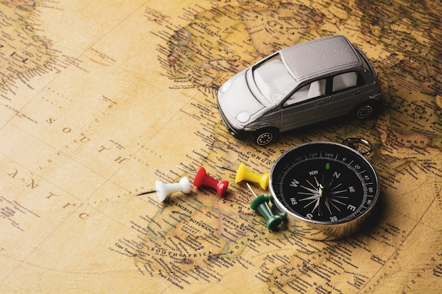 Compass and pushpin pile on a antique map. - travel and adventure concept.