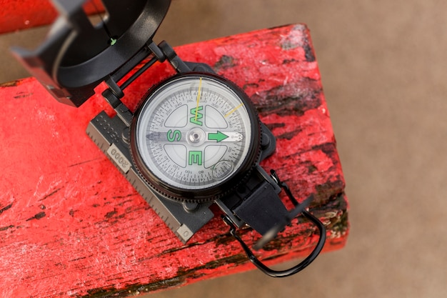 Compass on red piece of wood