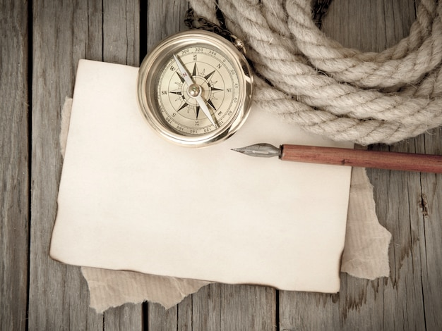 Compass, rope, pen and old paper on a wooden background top view