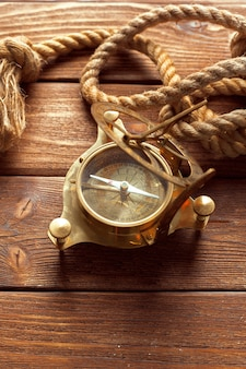 Compass and rope on wooden table.