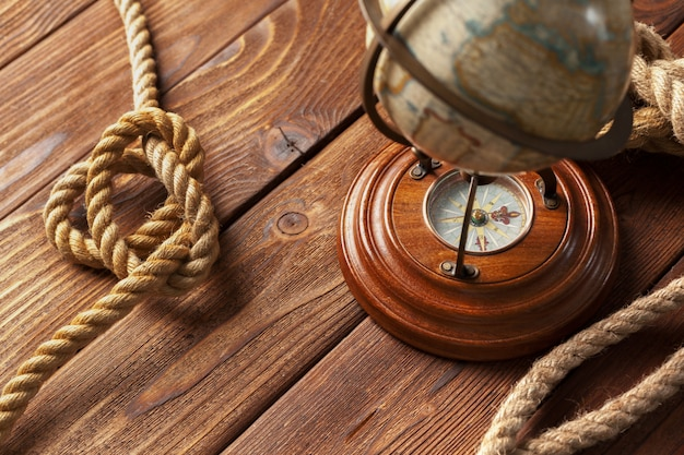 Compass and rope on wooden table