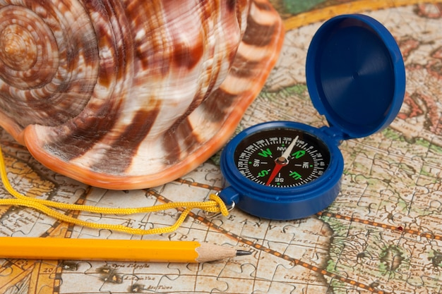 Compass and seashell on the map