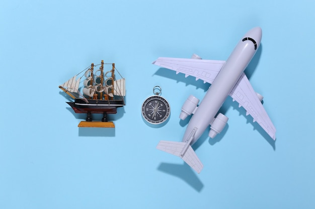 Compass, ship and air plane on bright blue