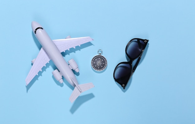 Compass, sunglasses and air plane on bright blue