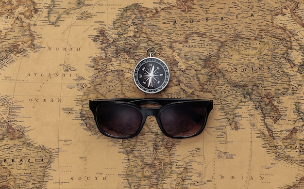 Compass and sunglasses on old map. travel, adventure concept