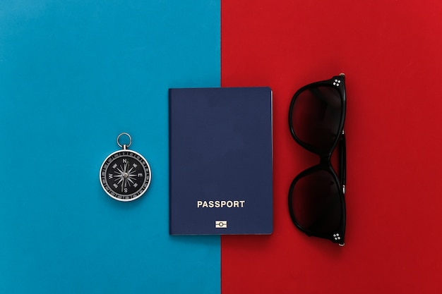 Compass, sunglasses and passport on a red-blue