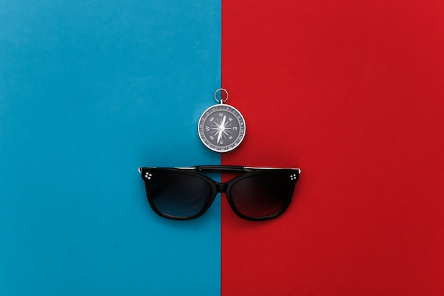 Compass and sunglasses on a red-blue