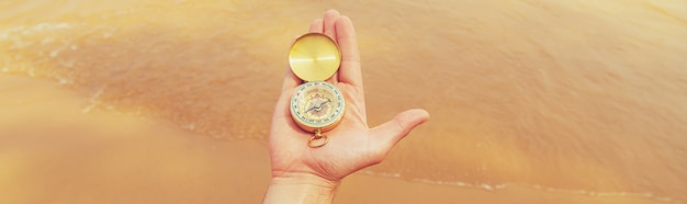Compass on the surface of the sea and the beach