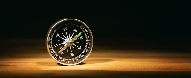 Compass on table on dark background