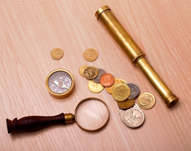 나무 테이블에 나침반, 망원경, 돋보기 및 동전