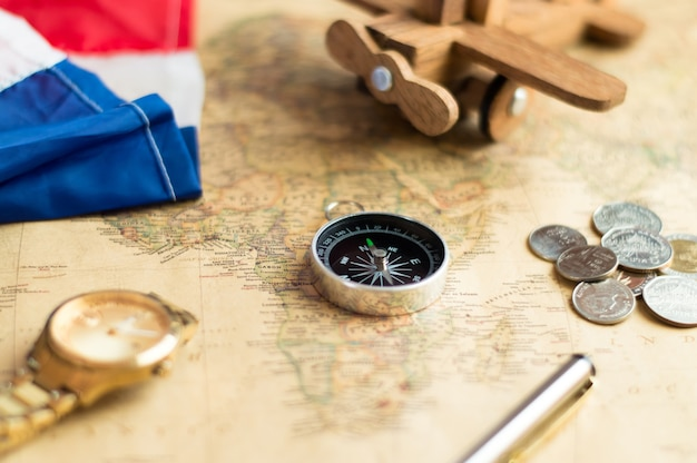 Compass on vintage world map with coins, pen, wrist watch, plane, flag for vacation travel