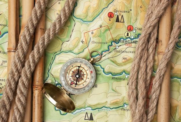 Компас с веревками и бамбуком на топографической карте