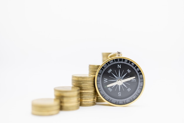 Compass with stack of gold coins on white.