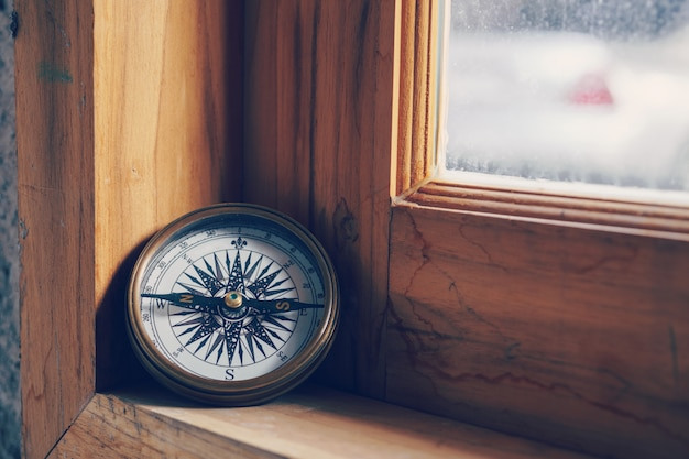 Compass on wooden window for travel and navigation concept