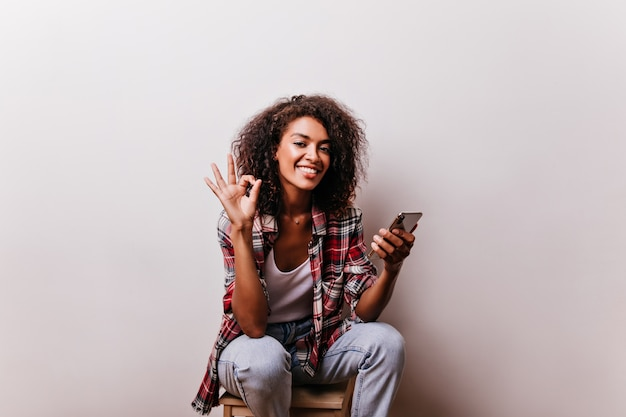 Compelling african girl posing with okay sign. curly black lady with romantic smile holding smartphone.