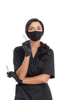 Грамотный косметолог в медицинской форме, маске и перчатках держит в двух руках шприцы для ухода за кожей.