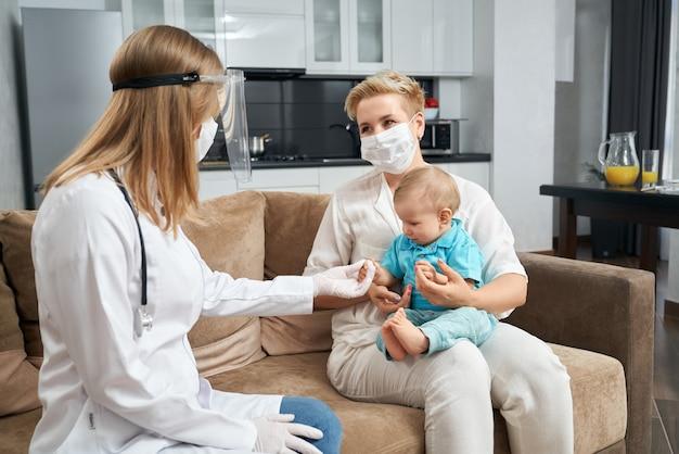 집에서 아기를 검사하는 마스크에 유능한 의사 프리미엄 사진