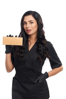 Компетентная женщина-косметолог в черной униформе и перчатках позирует с косметической коробкой в руке