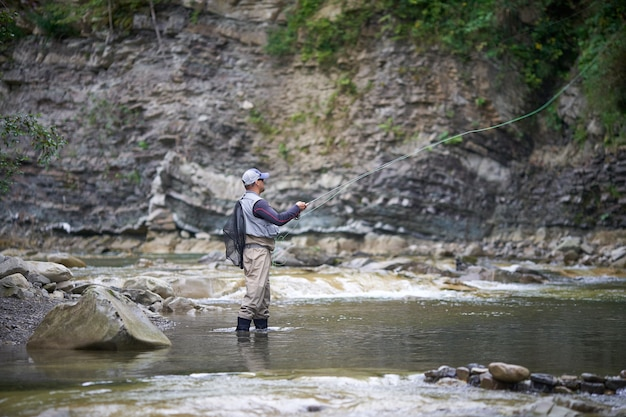 Competent fisherman in uniform and cap hooking with rod in rough river among mountains. concept of fishery and favorite hobby.