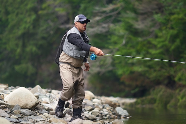 Competent fishermen in cap, glasses and waterproof outfit fishing with rod among mountains. man standing in river and catching fish on hook.