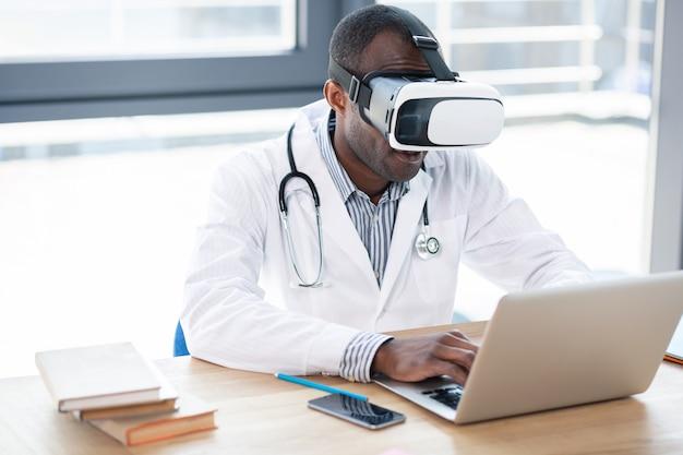 Компетентный международный медицинский работник, опираясь руками на стол во время печати диссертации