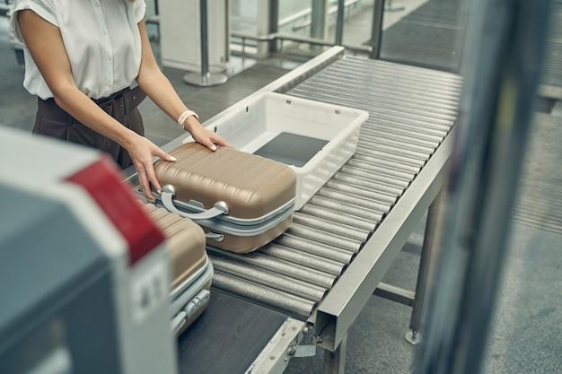 Компетентная путешественница кладет чемоданы на ленту для прохождения рентгеновского обследования перед полетом