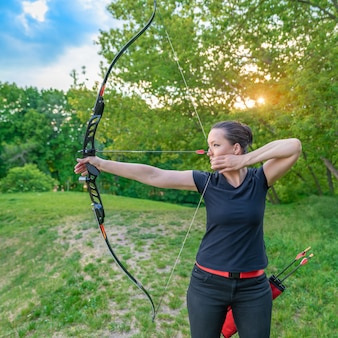 Competition in archery in nature. a young attractive woman points an arrow at a target