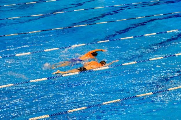 スイミングプールでの競争お互いを追い越そうとしている2人のスイマースポーツ健康的なライフスタイルの概念