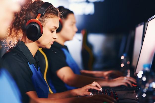 コンペ。焦点を絞った混血の少女、オンラインビデオゲームをプレイし、eスポーツトーナメントにチームと参加しているヘッドフォンを身に着けている女性のサイバースポーツゲーマーの側面図