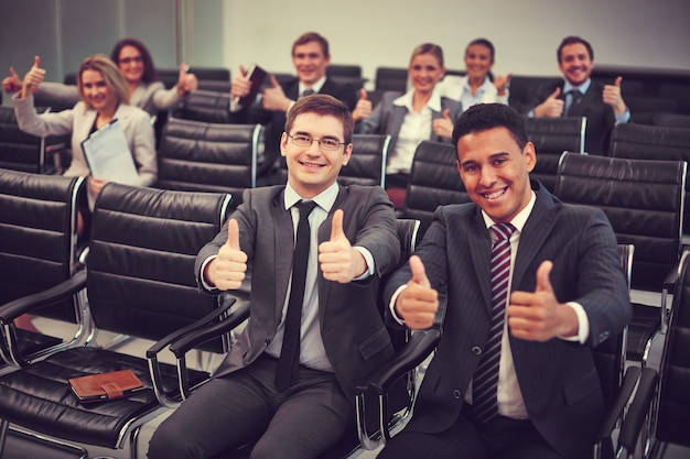 Competitive businesspeople with thumbs up