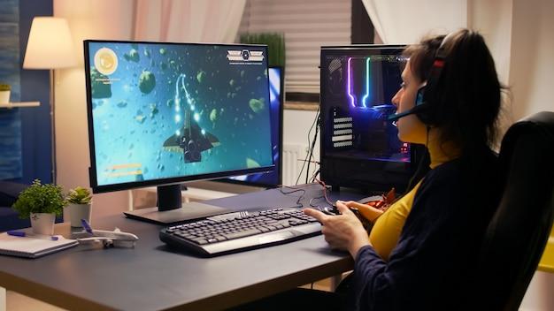 プロのヘッドセットを身に着けている競争力のあるサイバーゲーマーがオンラインビデオゲームトーナメントに勝つ