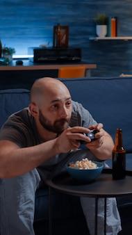 Соревновательный и решительный мужчина, играющий в видеоигру в гостиной ночью, сосредоточился на еде попкорна, наслаждаясь свободным временем