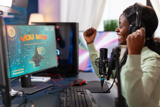 Competitive excited afro e sport player wining live competition celebraring championship. online streaming cyber performing during video games tournament in home with neon lights.