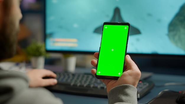 ライブトーナメント中に強力なコンピューターでオンラインゲームをプレイするグリーンスクリーンクロマキーデスクトップを備えたスマートフォンを見ている競争力のあるゲーマー。モックアップ分離ディスプレイと電話を使用してサイバープレーヤー