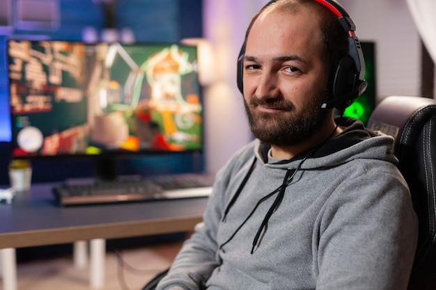 Соревновательный геймер смотрит на мощный компьютер, играя в онлайн-шутер поздно ночью с гарнитурой vr и беспроводной консолью. виртуальная онлайн-трансляция кибер-выступления во время игрового турнира