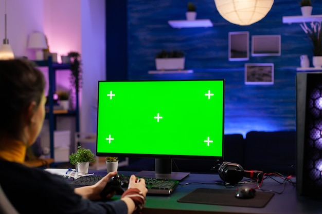 Competitive gamer looking into powerful pc with green screen display playing online games for live tournament. cyber player using pc with mock up chroma isolated desktop streaming shooter games