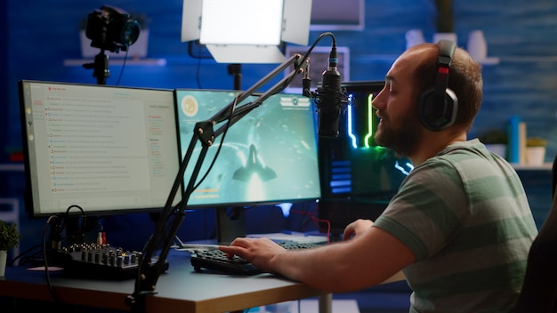 夜遅くにオンラインシューティングゲームをプレイする強力なコンピューターでストリームチャットを使用するヘッドフォンを使用する競争力のあるゲーマー。ゲームトーナメントで演奏する仮想オンラインストリーミングサイバーチェックサウンド