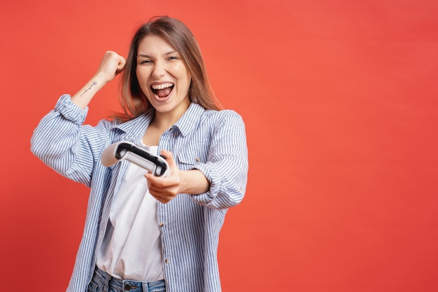 Competitive girl celebrates winning holding game joystick controller on red wall.