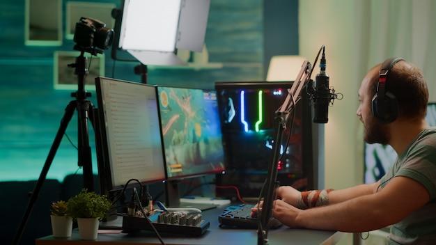 競争力のあるプレーヤーストリーミングeスポーツトーナメントチェックサウンドミキサー、ストリームチャット、プロのマイク。強力なコンピューターでオンラインスペースシューティングゲームの競争をしている競争力のある男