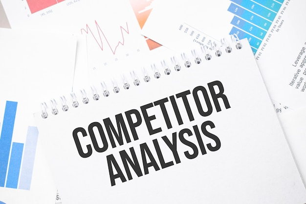 Competitor analysis text on paper on the chart surface with pen