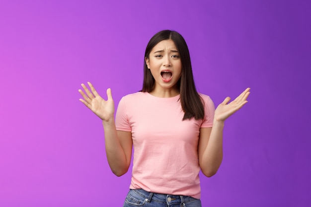 Complaining arrogant asian girlfriend whining cruel world, yelling crying being nasty, spread hands sideways bothered, feel unfair and displeased, look offended, stand purple background.
