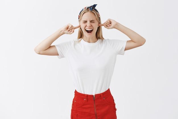 Giovane ragazza bionda infastidita lamentarsi che posa contro il muro bianco