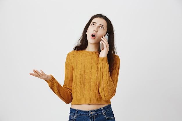 欲求不満の少女が電話で議論し、話し、目を転がして動揺