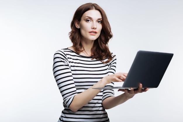완전한 피니셔. 회색에 고립 된 포즈를 취하는 동안 그녀의 노트북에서 작업하는 스트라이프 풀오버에 즐거운 꽤 적갈색 머리 여자