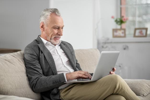 작업을 완료하십시오. 그의 직업을 즐기고 그의 컴퓨터 앞에 앉아있는 동안 긍정적 인 기뻐 수염 난 남성 다리를 건너