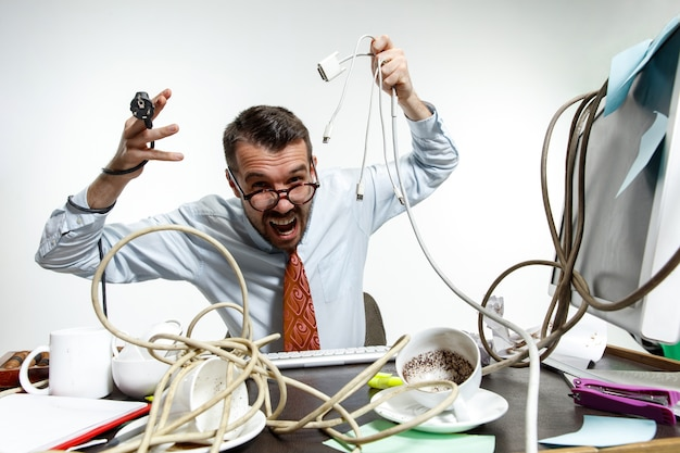 Completely confused. there are a lot of wires in the workplace and man is constantly tangled in them. concept of office worker's troubles, business, problems and stress.