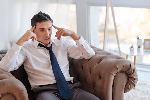 Полностью измотан. эмоциональный, вдумчивый умный мужчина чувствует себя совершенно измотанным, сидя в кресле после потери работы