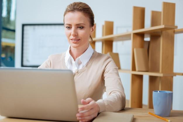 完全に占有されています。オフィスに座って興味を示しながらコンピュータを使用して気配りのある秘書のクローズアップ
