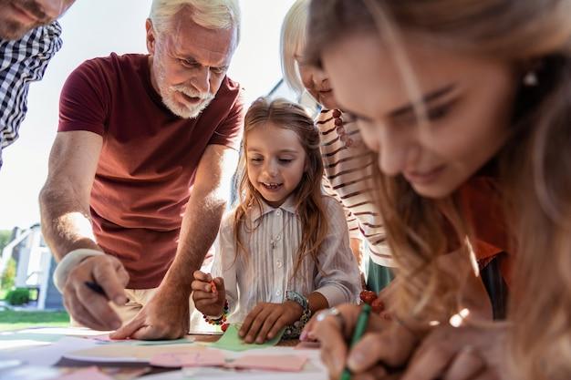작업 완료. 손녀를 도우면서 긍정을 표현하는 잘 생긴 수염 할아버지