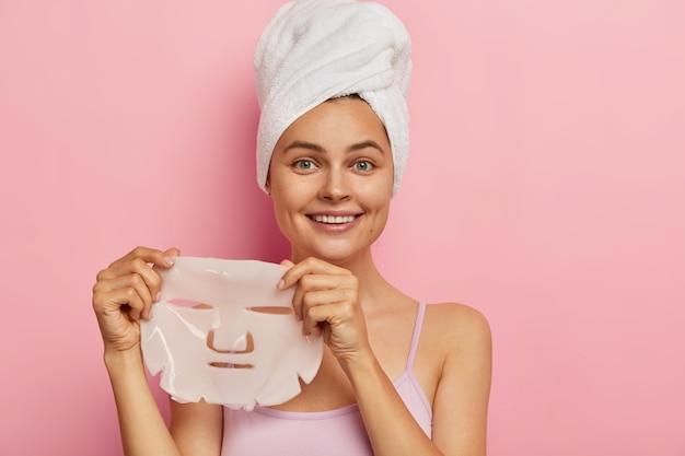 Concetto di trattamento della carnagione. la giovane donna graziosa tiene la maschera di buccia di gel per il viso, ha un'espressione allegra, indossa un asciugamano sulla testa dopo aver fatto il bagno, vestita in abbigliamento casual